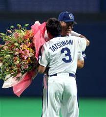引退セレモニーで立浪から花束を受け取り抱き合う井上一樹=ナゴヤドーム