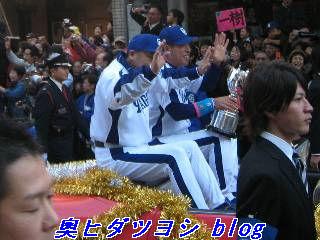 赤いオープンカーに乗っている落合博満監督(左)と井上一樹選手会長=日本一パレード