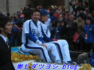 白いオープンカーに乗っている立浪和義(左)と中村紀洋=日本一パレード
