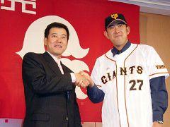 巨人のユニホームを着て原監督(左)と握手する門倉健投手