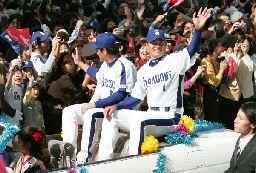 中日の優勝パレードで、沿道のファンに手を振る福留孝介外野手(右)と川上憲伸投手=3日午前、名古屋市中区