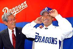 奈良原(右)は中日のユニホームに袖を通し、伊藤球団代表の励ましに笑顔を見せる=中日球団事務所