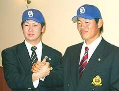 仮契約をかわし握手する法大・西川明(左)と名城大・清水昭信