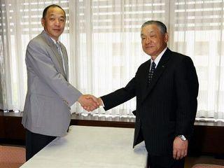 前半戦終了の報告を終えて握手する落合監督(左)と白井オーナー=名古屋市中区