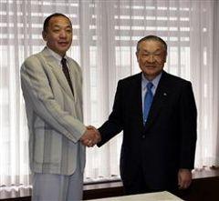 握手を交わす白井オーナー(右)と落合監督=名古屋市中区