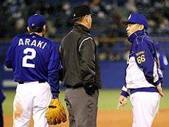 3回表、1死一塁、井端の三ゴロで一走荒木(左)がアウトになった判定について、橘高三塁塁審に抗議する落合監督(右)=神宮