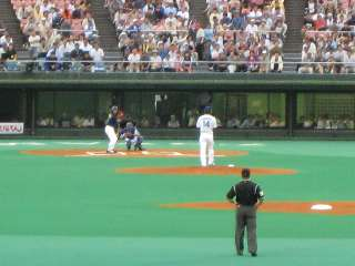 プレイボールで先発朝倉健太が第1球目を投げる