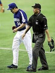 2回裏、井野球審(右)に不調を訴えベンチに戻る山本昌=東京ドーム